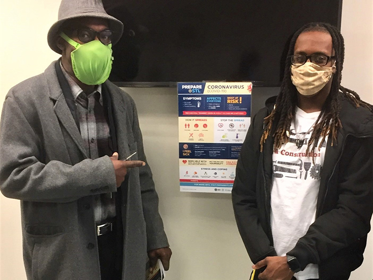 Terrez, right, puts up PrepareSTL poster at Employment Connection with instructor Calvin Burks.