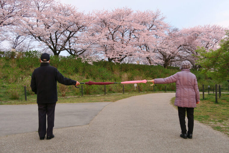 Two elderly people standing 6 feet apart